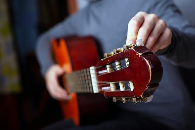 De muzikant stemt een akoestische zes-snarige gitaar.