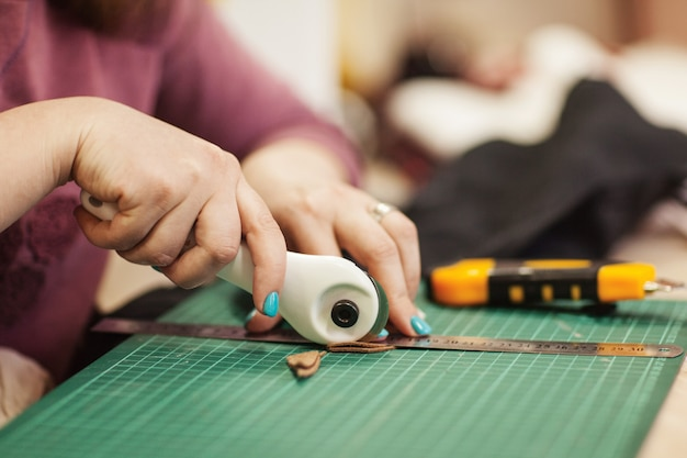De naai-master knipt een stuk stof af voor verder werk.