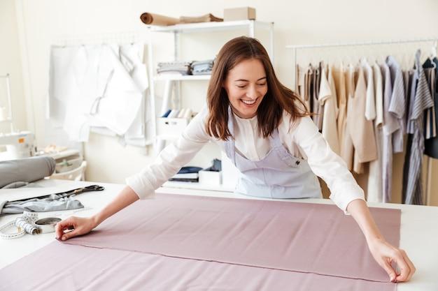 De naaister het uitspreiden van de vrouw stoffen in workshop