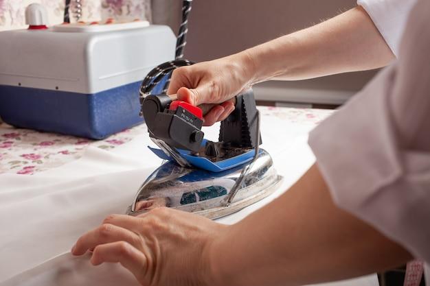 De naaister in het atelier strijkt de jurk met stippen op tafel met een professioneel strijkijzer