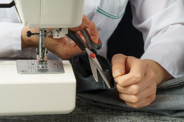 De naaister snijdt de draad door tijdens het knippen en naaien van kleding