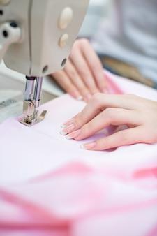 De naaister van het meisje naait op de naaimachine