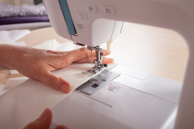 De naaisters zijn muf op de naaimachinedetails van kleding gemaakt van stof