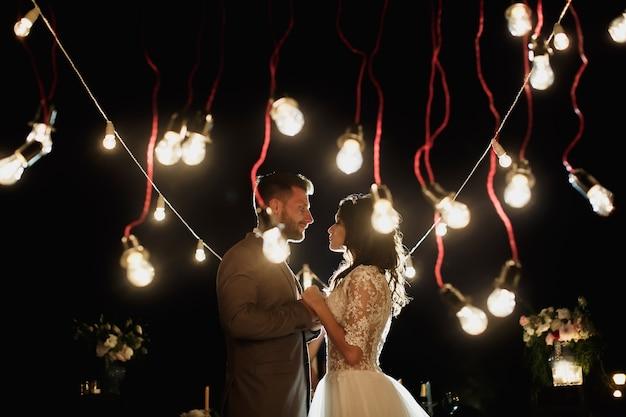 De nachtelijke huwelijksceremonie. bruid en bruidegom kijken elkaar op de achtergrond aan