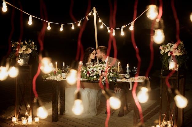 De nachtelijke huwelijksceremonie. de bruid en bruidegom zitten aan de feestelijke tafel. banket
