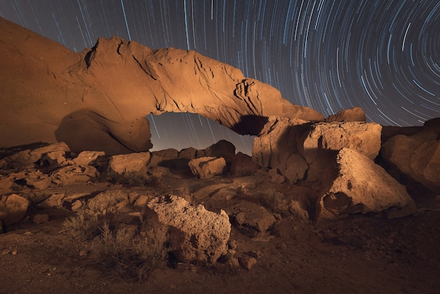 De nachtlandschap van sterslepen van een vulkanische rotsboog in tenerife, canarische eilanden, spanje.