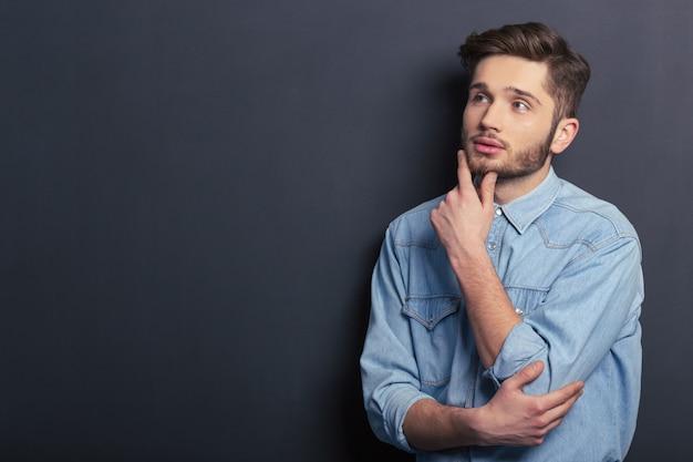 De nadenkende jonge mannelijke student kijkt weg.
