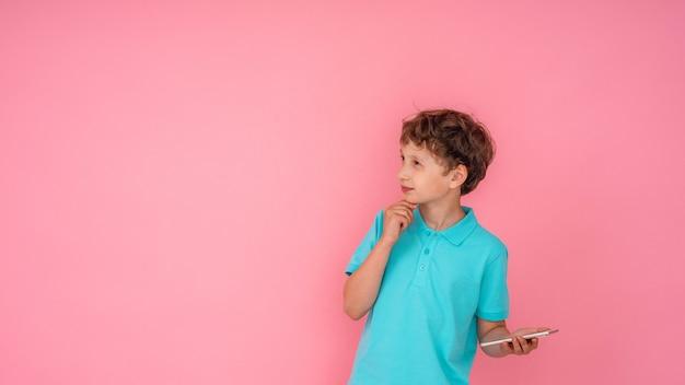 De nadenkende jongen houdt smartphone in zijn handen en kijkt weg op roze.