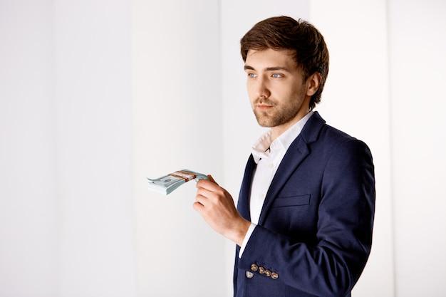 De nadenkende knappe zakenman die contant geld houden en kijkt weg, nadenkend hoe geld in zaken te investeren