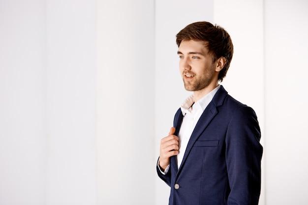 De nadenkende knappe zakenman in kostuum, overweegt mening van zijn bedrijfsbureautoren, tevreden glimlachen