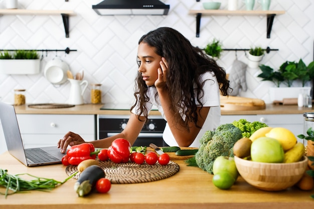 De nadenkende mooie mulatvrouw kijkt op het laptop scherm op de moderne keuken op de tafel vol met groenten en fruit, gekleed in wit t-shirt
