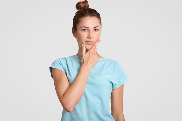 De nadenkende, verbaasde vrouw met aarzelende uitdrukking, houdt haar kin vast, gekleed in vrijetijdskleding, denkt ergens over na