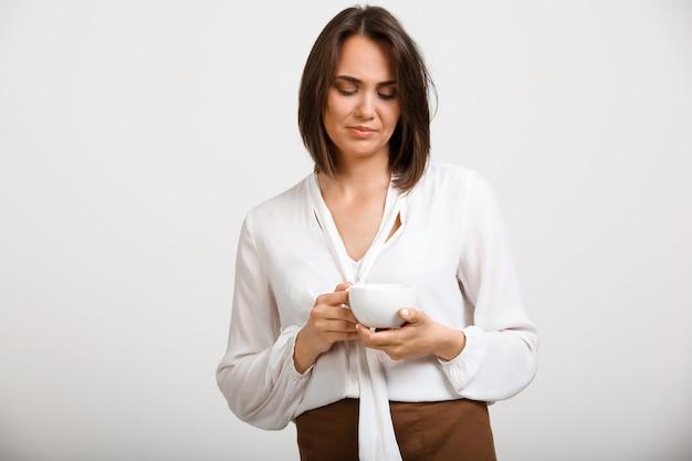 De nadenkende verstoorde maniervrouw drinkt koffie, denkend