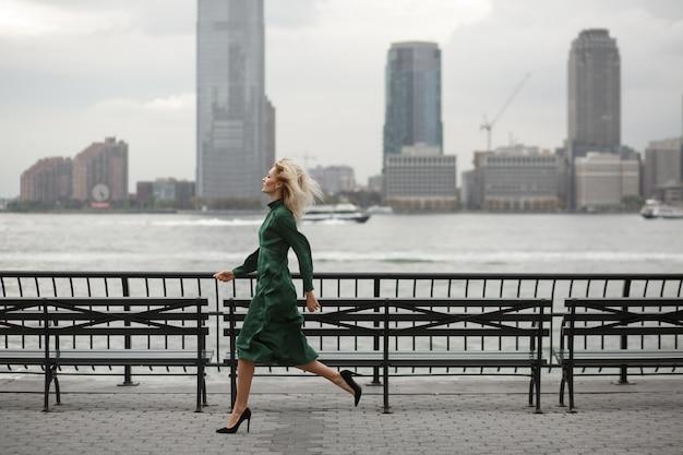 De nadenkende vrouw loopt in haar elegante kleding langs de rivierkust in new york
