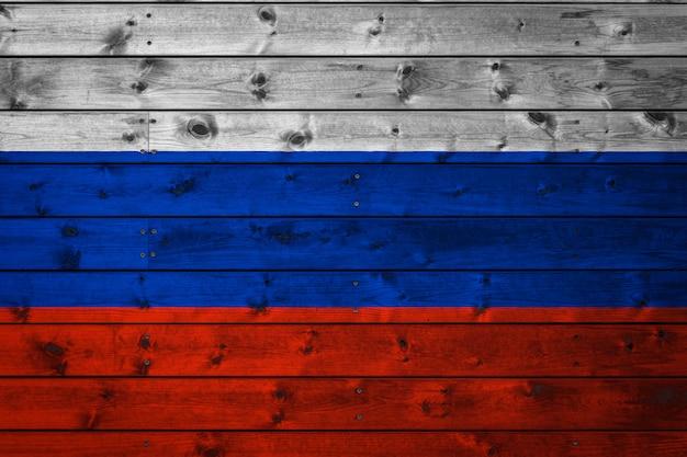 De nationale vlag van rusland is geschilderd op een kamp van zelfs planken die met een spijker zijn genageld