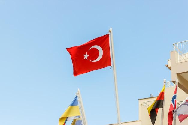 De nationale vlag van turkije die in de wind tegen een blauwe hemel blazen