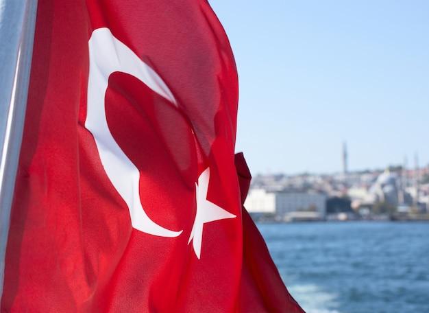 De nationale vlag van turkije tegen de wateren van de bosporus en de stadsgebouwen van istanbul