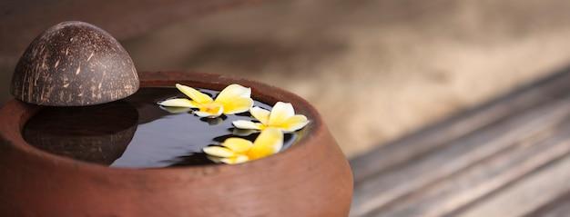 De natuur aanraken. kleikruik ontspannend en vredig met bloemplumeria of frangipani versierd op water in kom in zen-stijl voor spa-meditatiestemming