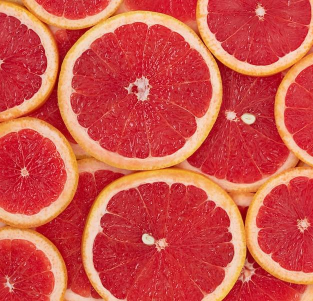 De natuurlijke achtergrond van rode rijpe ronde schijfjes grapefruit