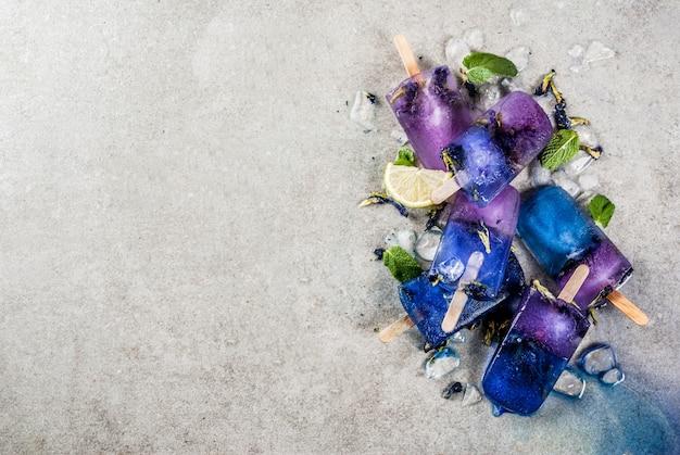 De natuurlijke organische eigengemaakte blauwe en violette roomijsijslollys van de zomersnoepjes met de bloem grijze concrete achtergrond van de vlindererwt