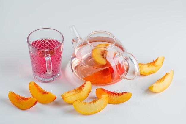 De nectarineplakken met de zomer drinken hoge hoekmening over een witte oppervlakte