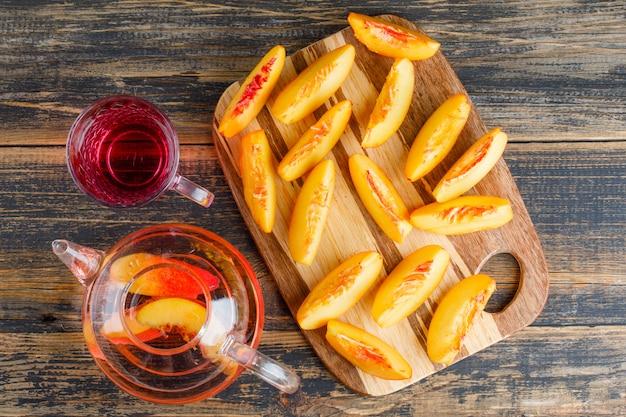 De nectarineplakken met drank op houten en scherpe raadslijst, leggen.