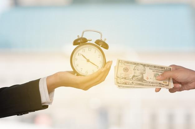 De niet geïdentificeerde bedrijfsmensenhanden tonen zwarte wekker en dollarbankbiljet