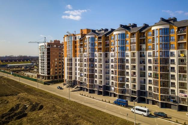 De nieuwe lange flatgebouwen en geparkeerde auto's en voorstadhuizen op blauwe hemel kopiëren ruimteachtergrond.