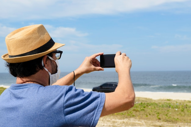 De nieuwe normale man van middelbare leeftijd maakt een foto van het strand