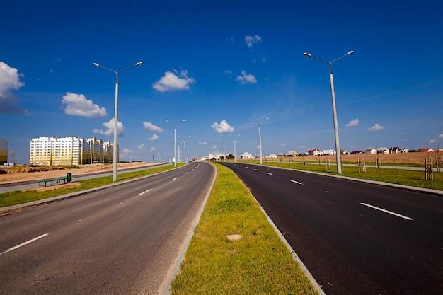 De nieuwe weg - de aangelegde nieuwe weg in de nieuwe wijk van de stad in aanbouw