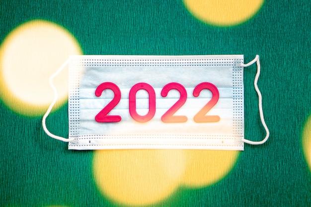 De nummers 2022 liggen op een medisch masker op een groene achtergrond. gelukkig nieuwjaar, kerstmis en gezondheidsconcept.