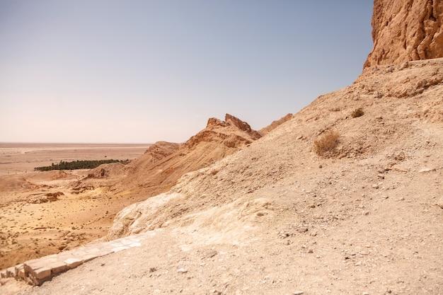 De oase van landschapschebika in de woestijn van de sahara. uitzicht op het berglandschap. toneelmeningsbergoase in noord-afrika. gelegen aan de voet van jebel el negueba. atlasgebergte op zonnige middag. tozeur, tunesië