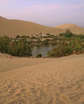 De oasisstad huacachina zoals die van het zandduin bij zonsondergang, ica-gebied, peru wordt gezien