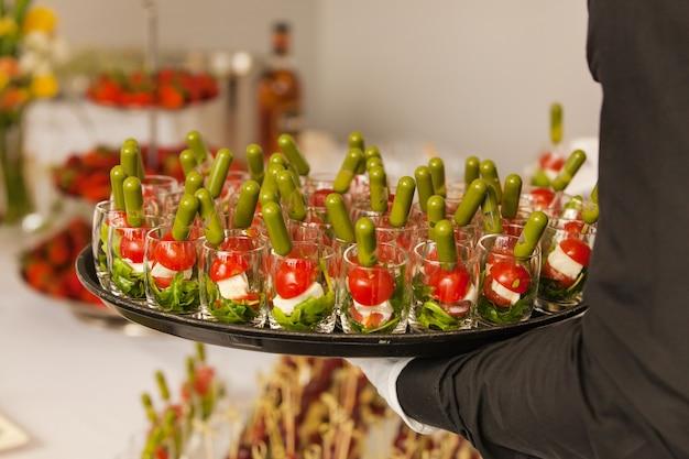 De ober brengt een dienblad met snacks op een feestelijk evenement, feest of bruiloft