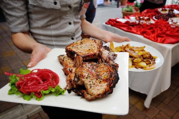 De ober brengt gefrituurde biefstuk en aardappelen