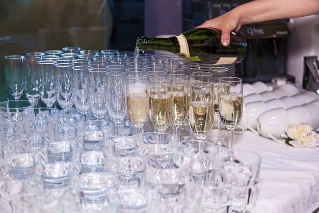 De ober giet champagne in glazen uit een fles in een restaurant. catering, banket