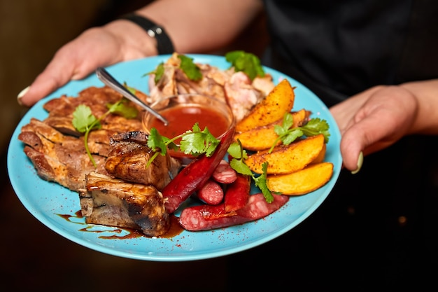 De ober houdt een bord met vleesschotel met gebakken aardappelen en tomatensaus vast