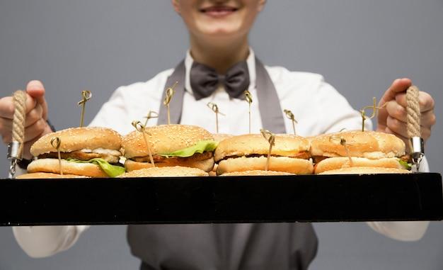 De ober houdt een dienblad met hamburgers in zijn handen. grijze muur.