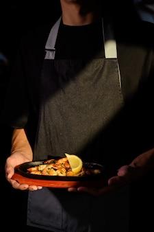 De ober houdt een garnaalschotel vast