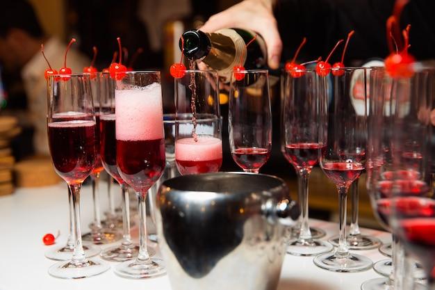 De ober schenkt champagne in de glazen aan de rand van het glas is een mousserende kersenwijn op een feestje