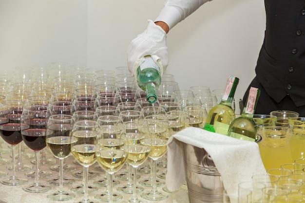De ober schenkt rode en gele wijn in wijnglazen