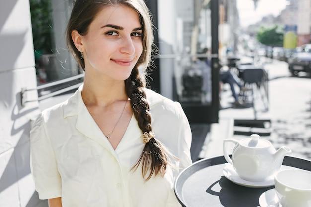 De ober van de gelukkige vrouw houdt een dienblad met keukengerei. restaurant service. service met een glimlach.