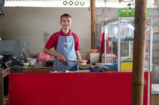 De ober van de kraam staat met een tang terwijl hij de bijgerechten bereidt die de klant in de winkel heeft besteld
