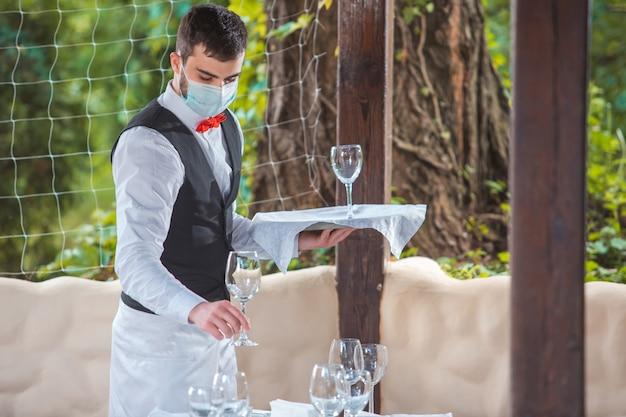 De ober werkt in een restaurant op het zomerterras