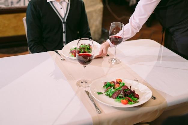 De ober zet de salade voor de gast op tafel