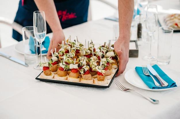 De ober zet een bord op tafel met gastronomische hapjes, diverse mini sandwiches, crostini met verschillende toppings. vooraanzicht hierboven. geassorteerde italiaanse voorgerecht bruschetta.