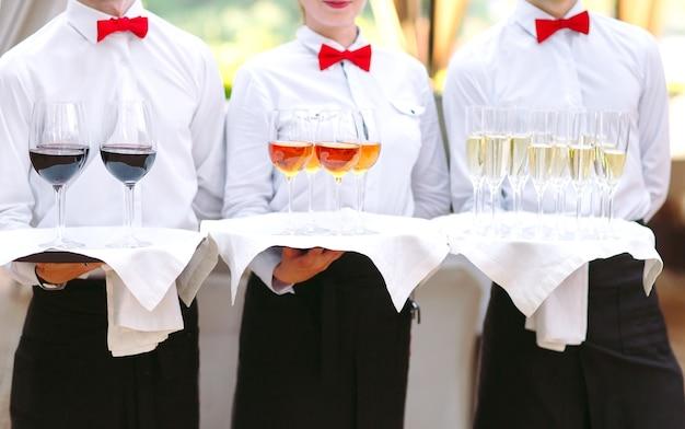 De obers begroeten gasten met alcoholische dranken. champagne, rode wijn, witte wijn op dienbladen.