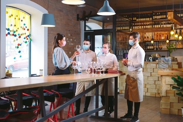 De obers van het restaurant met een medisch masker leren onderscheid te maken tussen de glazen