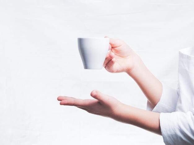 De obershand biedt een kopje koffie aan aan de hand van de bezoeker die een cappuccino-kop vasthoudt