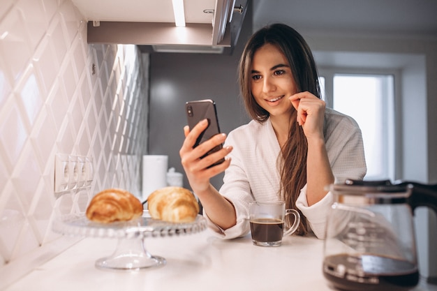 De ochtend van de vrouw met telefoon, croissant en koffie bij keuken